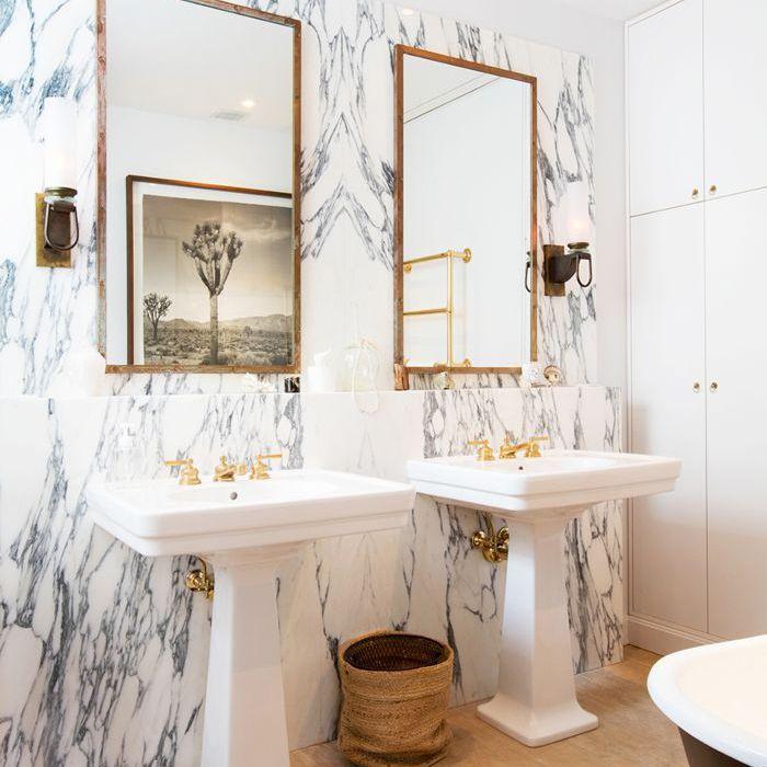 marble bathroom with twin pedestal sinks, wood floors