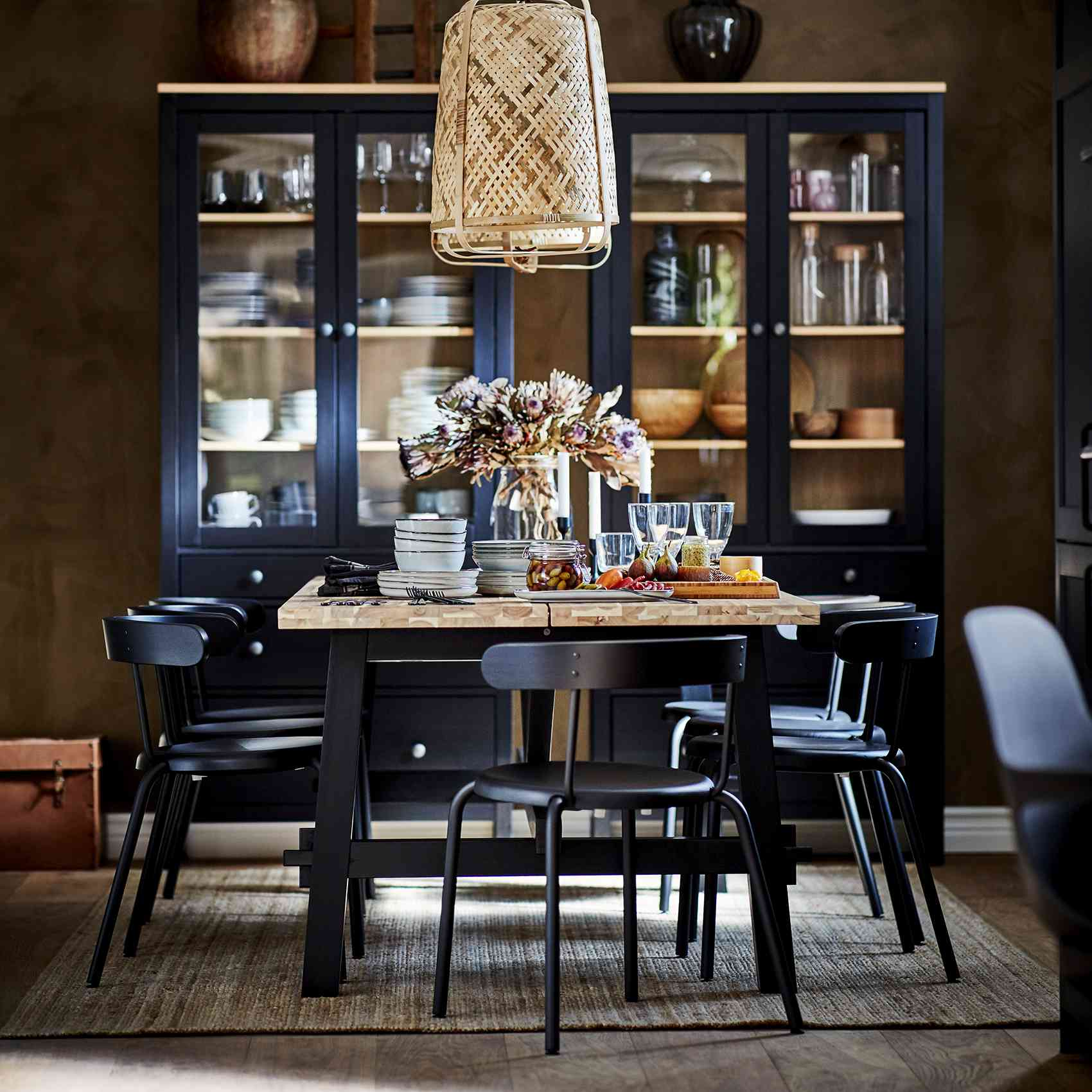 dining room with black chairs and rattan lighting