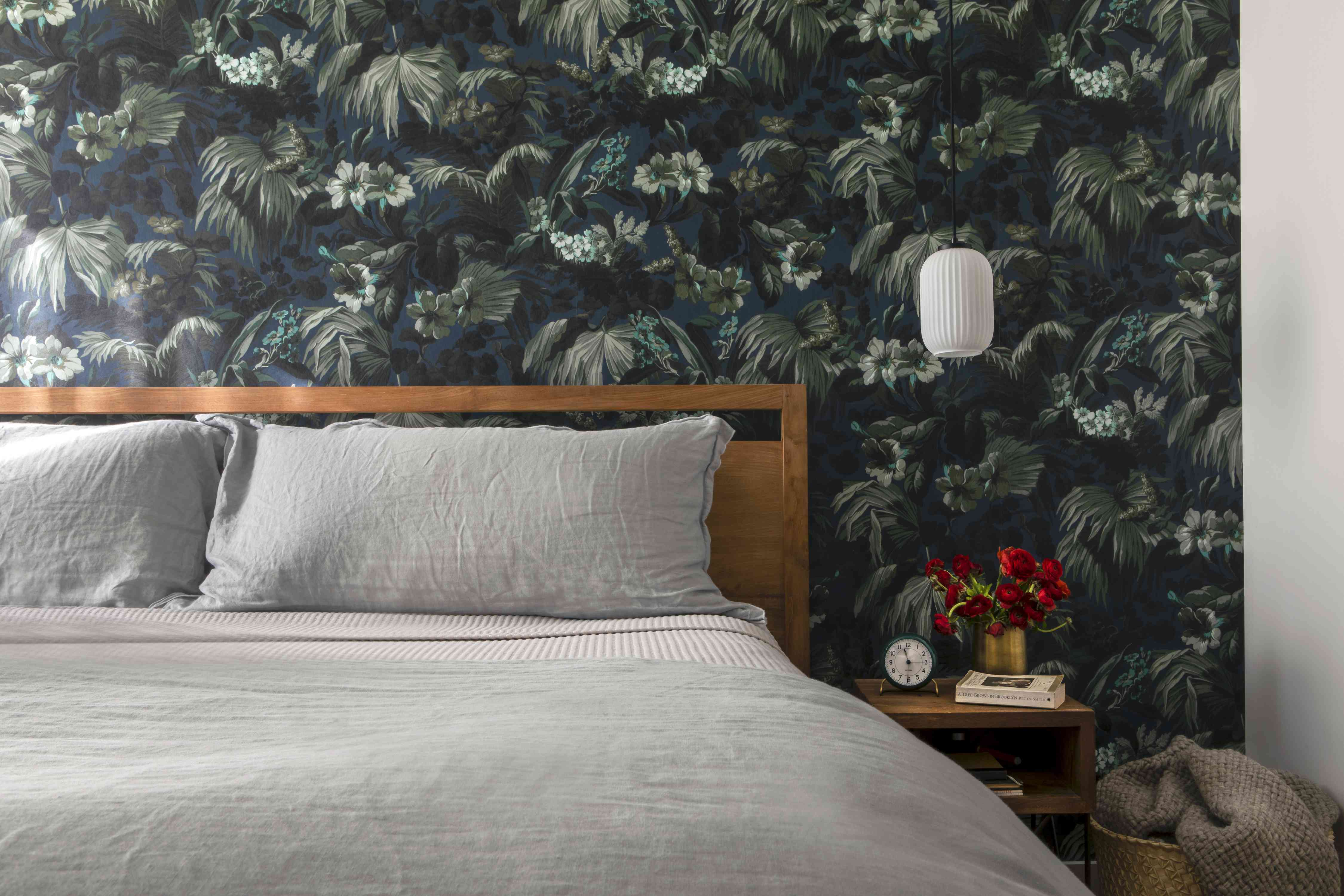 Bedroom with plant wallpaper.