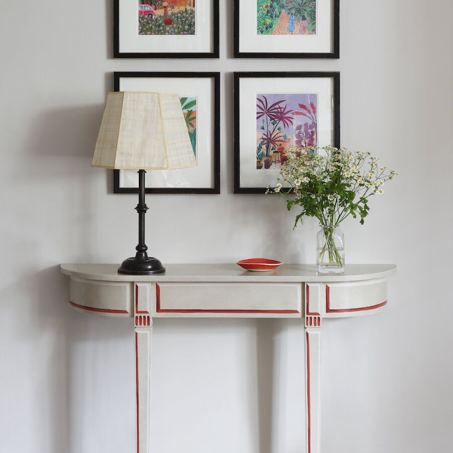 A small ivory console table near several colorful prints