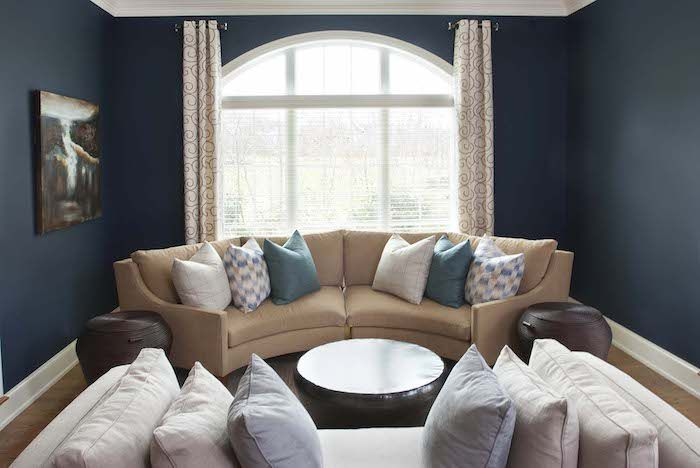 living room with dark blue walls, tan couch, single painting on the wall