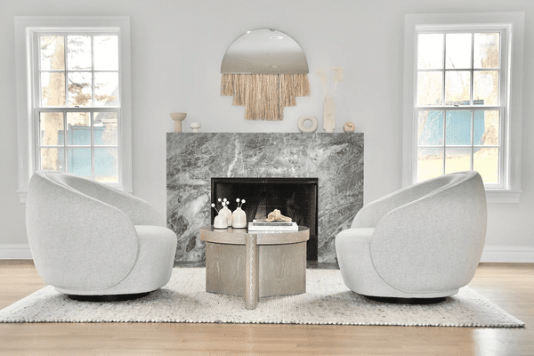 A bold living room with a gray marble fireplace and two circular chairs