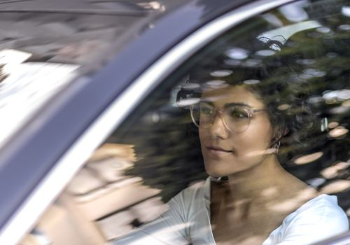 Young woman sitting in drivers seat of a black car, driving.