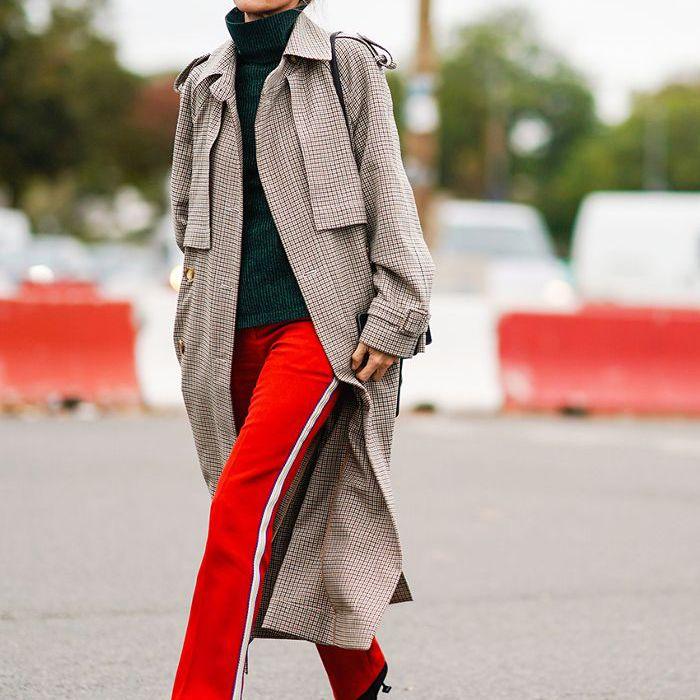 una mujer con trinchera, pantalones brillantes y tacones adornados