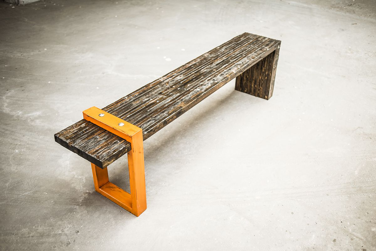 A reclaimed wood bench with an orange metal leg.