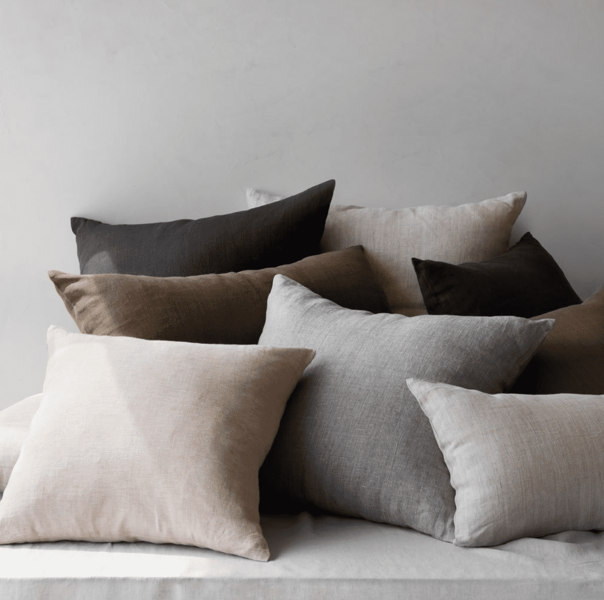 linen pillows in multiple earthy shades including olive, gray, and blush pink