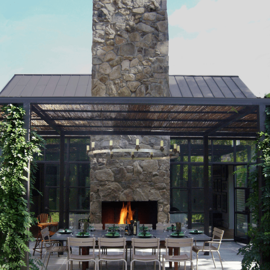 An outdoor dining room, situated near an outdoor fireplace with a tall, stone-lined chimney