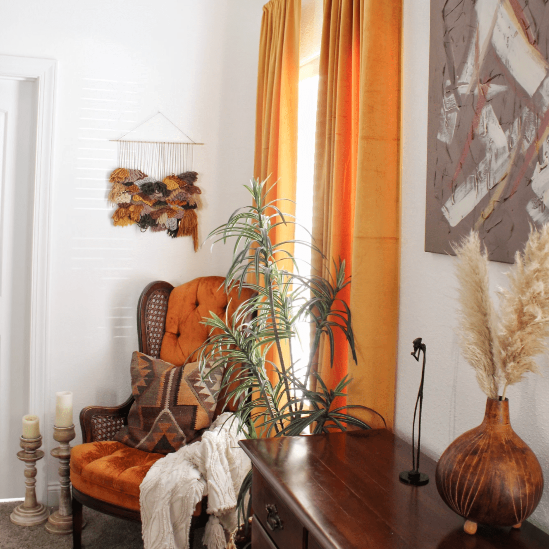A corner with orange curtains and wood furniture