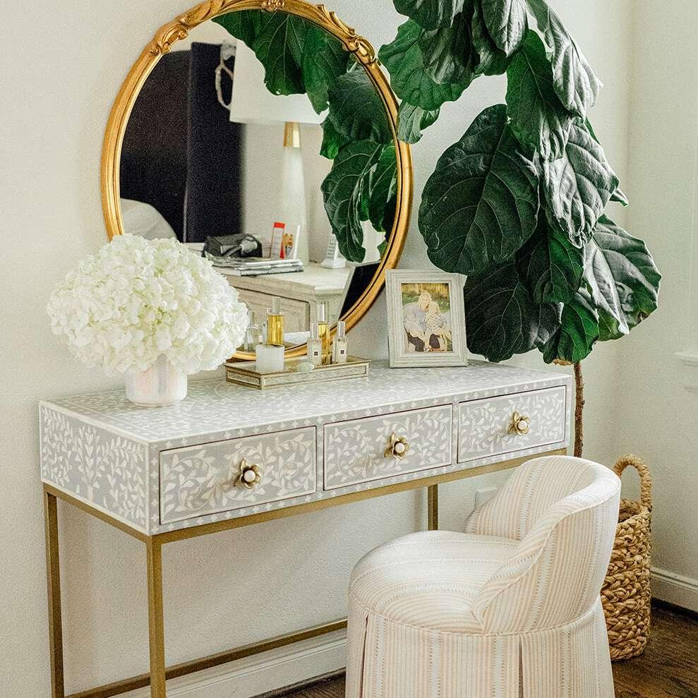 Elegant vanity setup with large faux fiddle leaf fig.