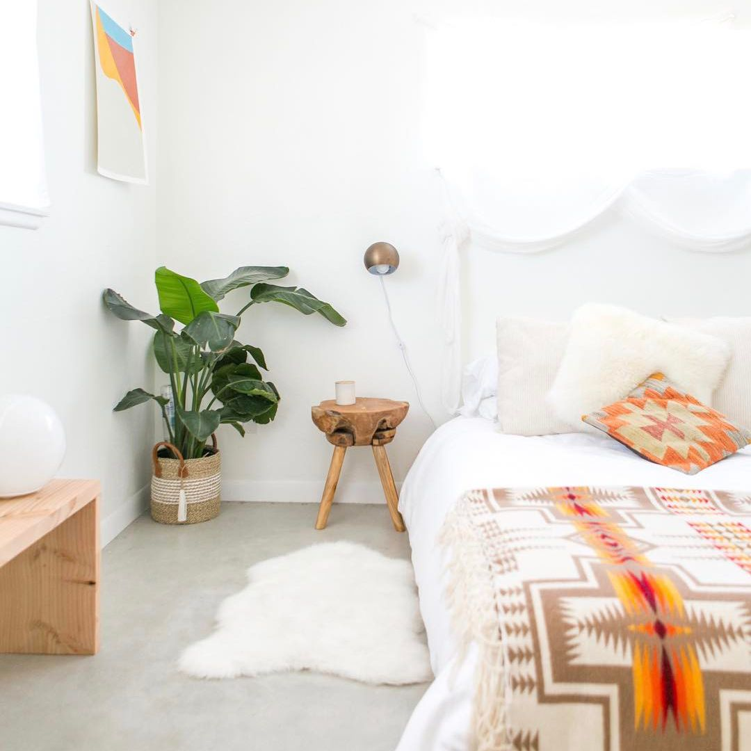 A white bed with orange printed blankets on it