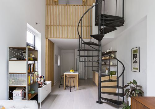 Overview of apartment with black spiral staircase.