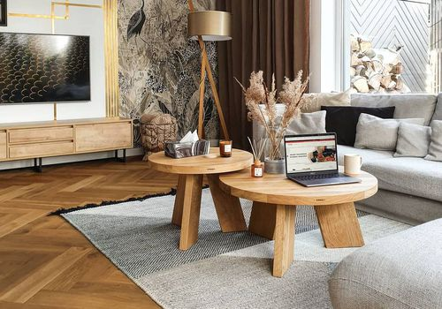 Wooden coffee tables on gray rug with mixed wood media stand and floor.
