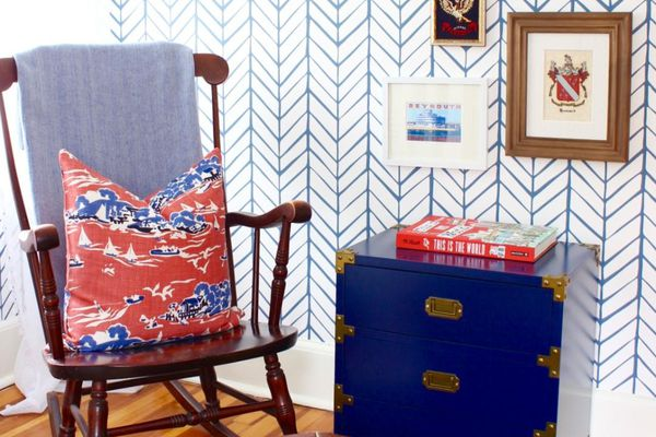 Corner of nursery with rocking chair and leather ottoman.