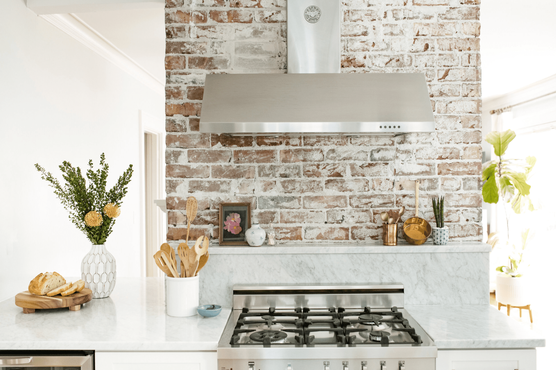 An exposed brick column, which has been turned into a kitchen backsplash