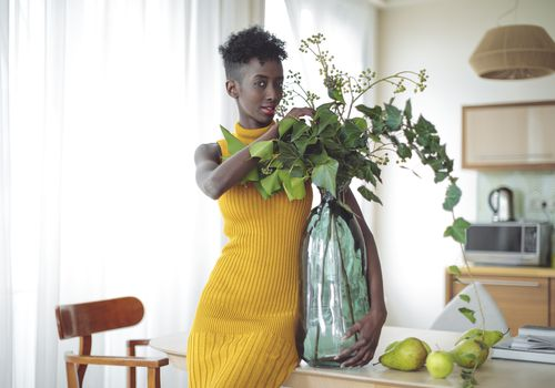 A young, black woman in a yellow dress, holding a large vase with a plant in it.