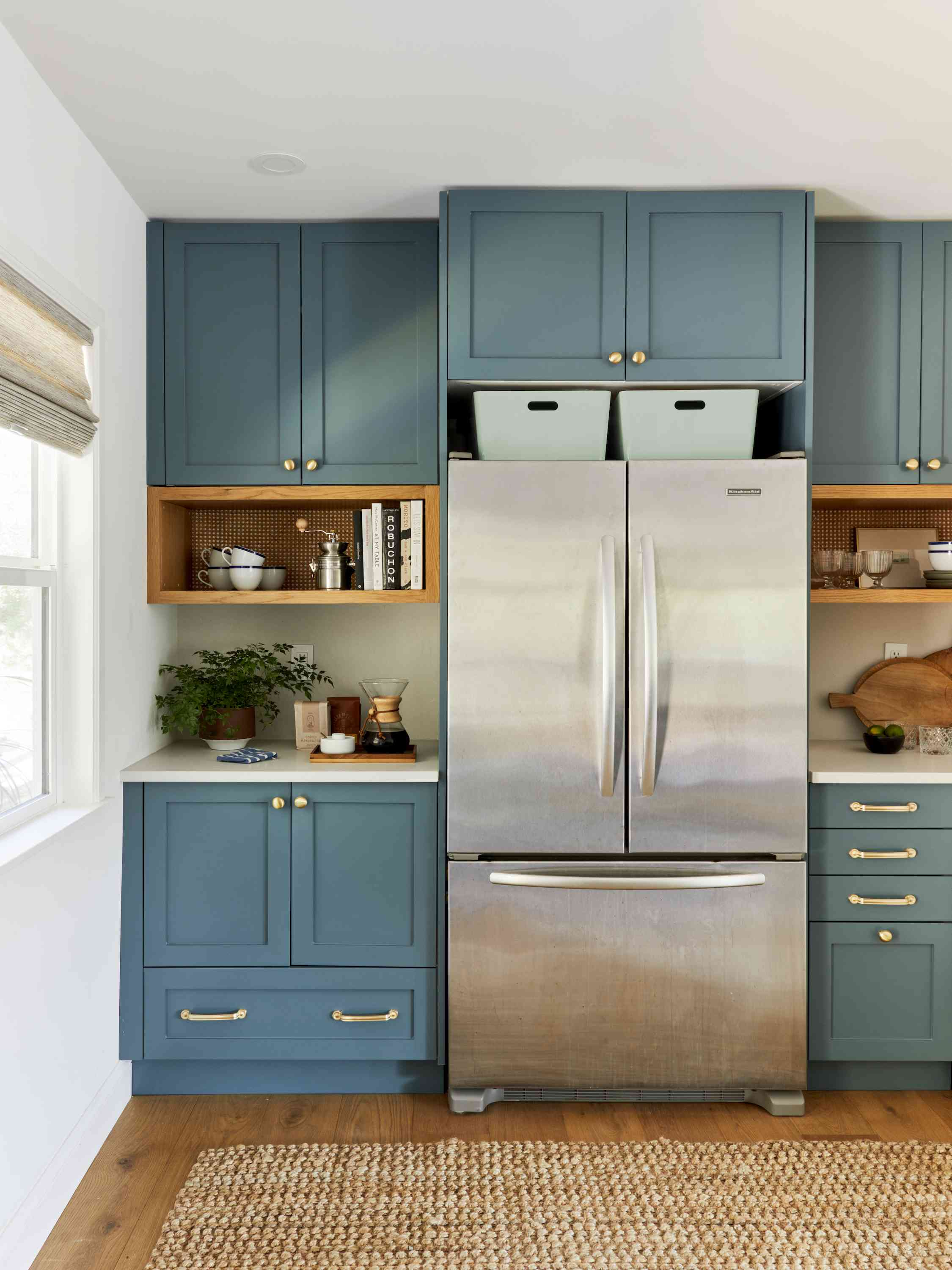 Stainless steel fridge with two drink cubby areas next to it.