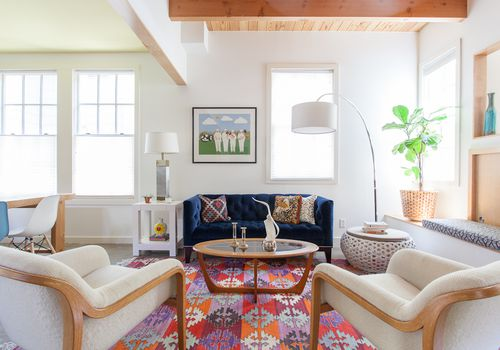 A furnished living room with a printed rug
