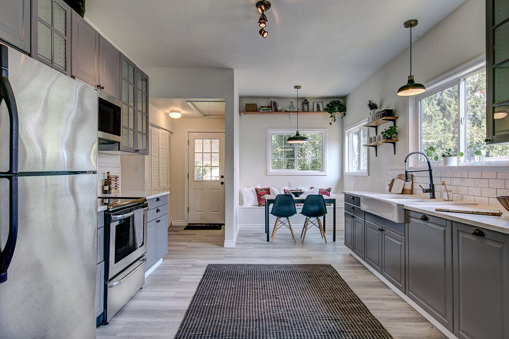 A spacious kitchen with gray cabinets and a dark gray rug