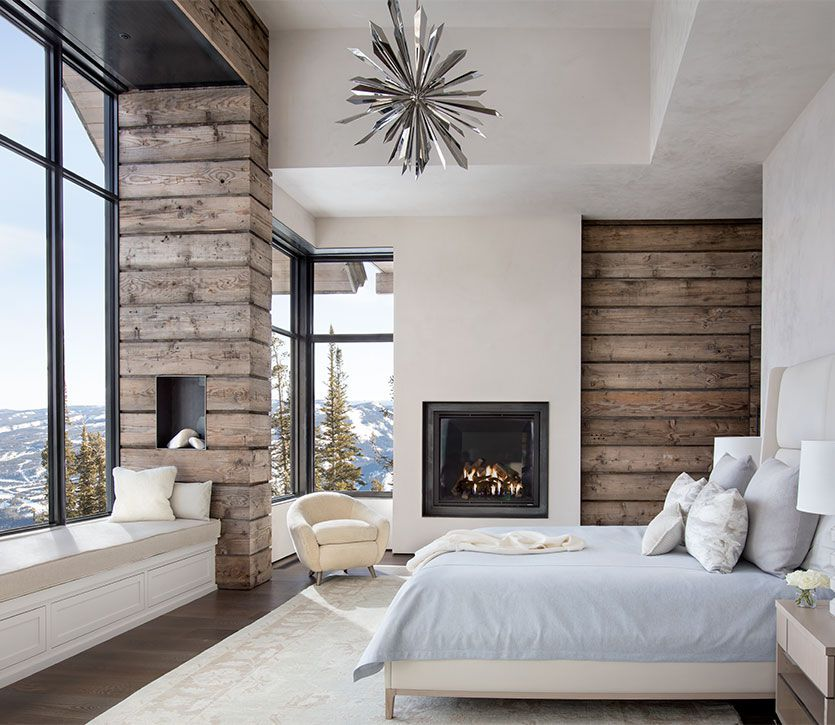 A wood-paneled room with a bed and a fireplace