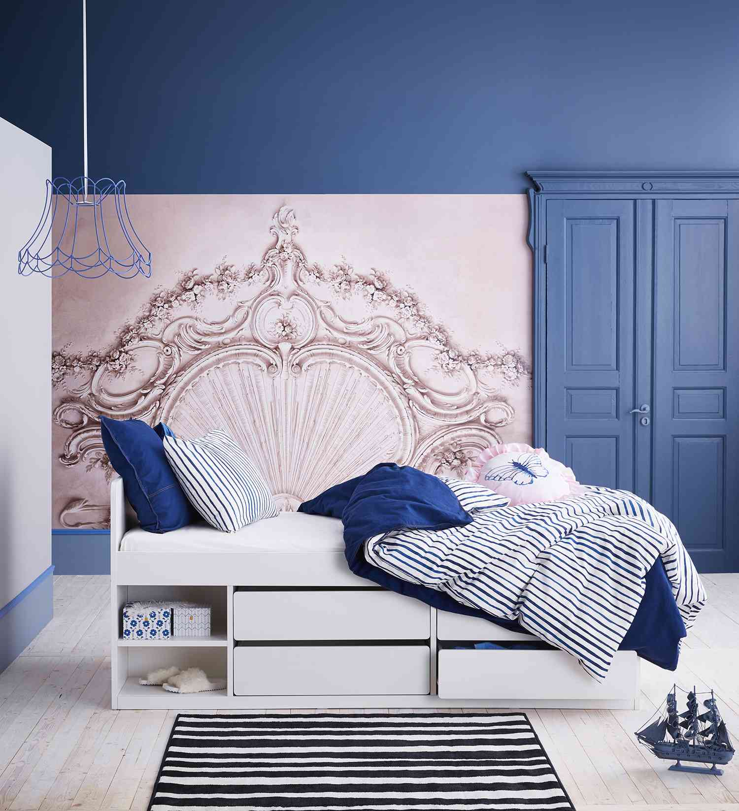 White twin bed with built-in storage against blue and pink walls