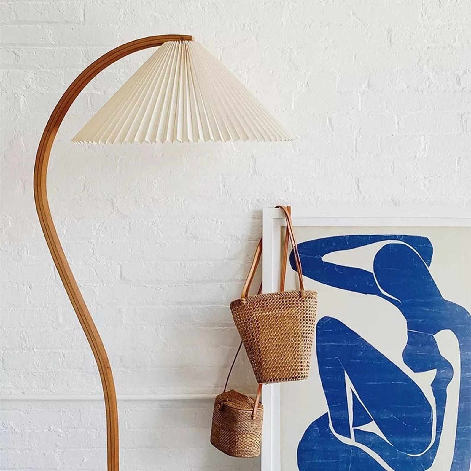 A wooden floor lamp with a pleated lamp shade, currently for sale at Etsy