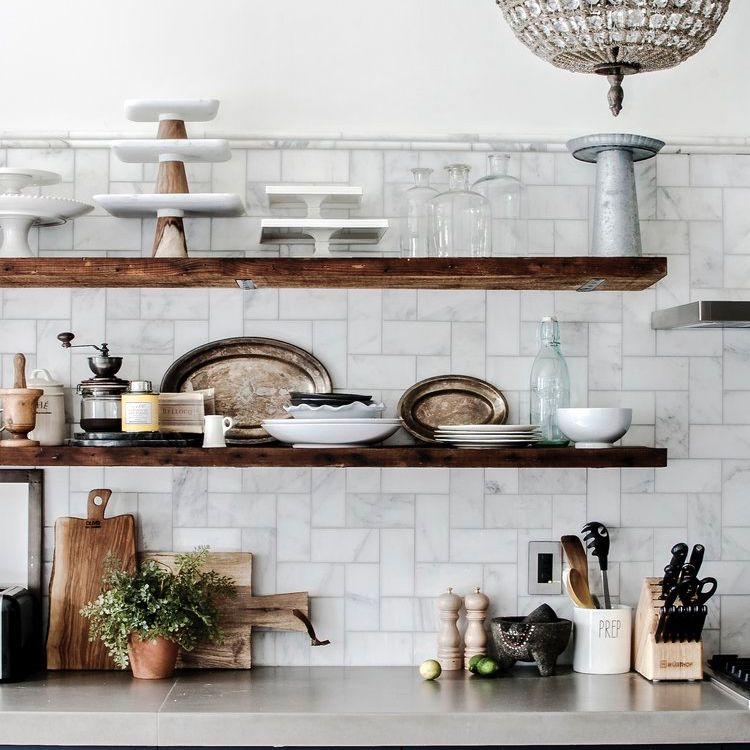 Kitchen with open shelves displaying antique cake stands and silver plates