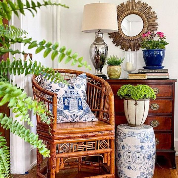 Bamboo chair next to dresser and plant.