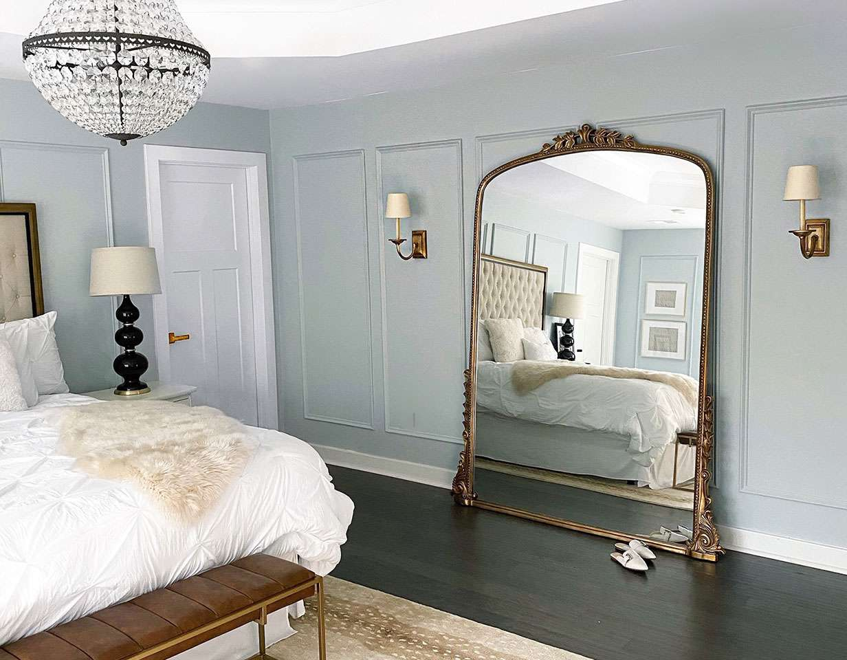 Bedroom with crystal chandelier and large leaning mirror.