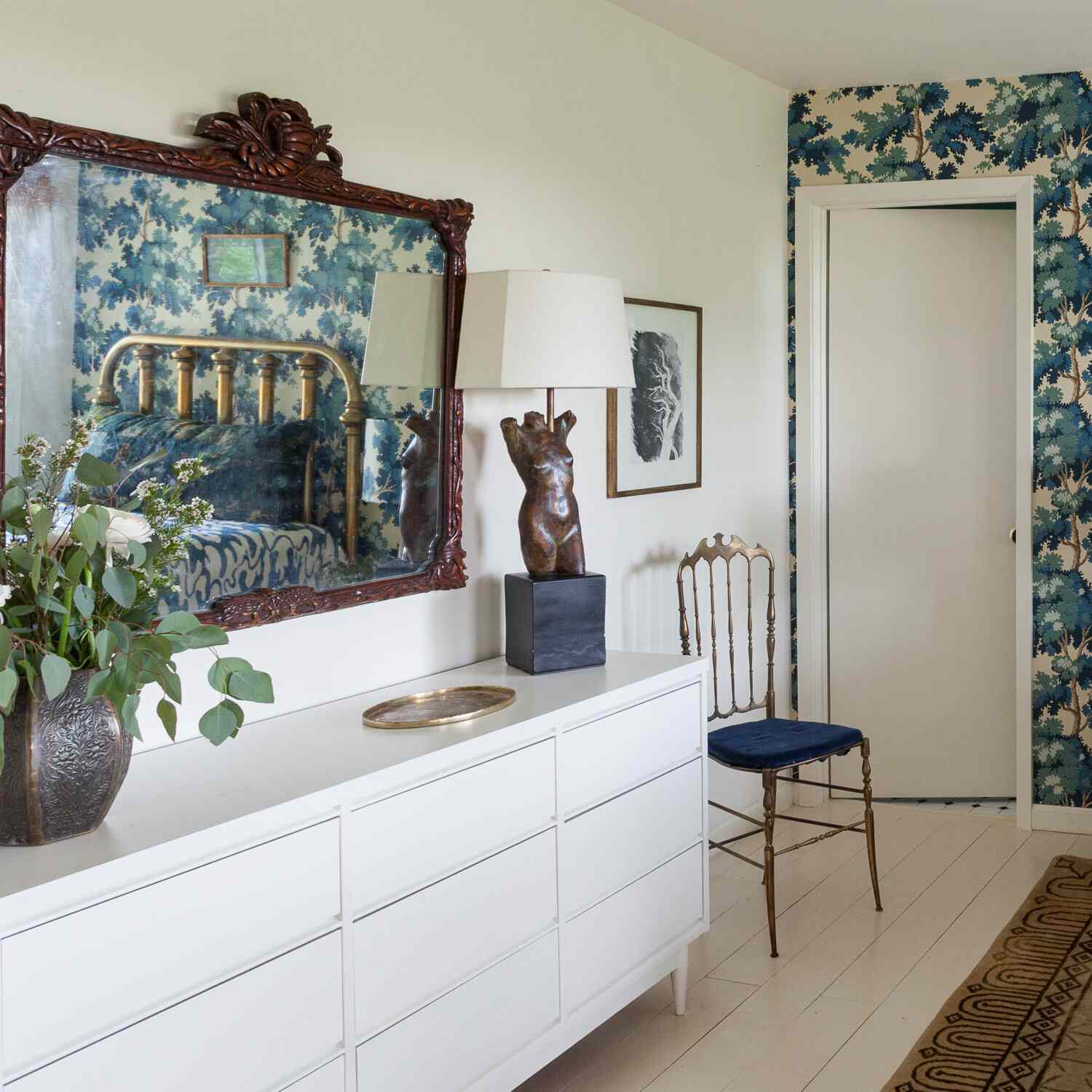 A bedroom mirror highlighting an accent wall covered in wallpaper