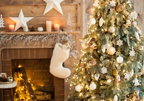 christmas tree decorated with white and gold ornaments in front of fireplace with stocking and presents