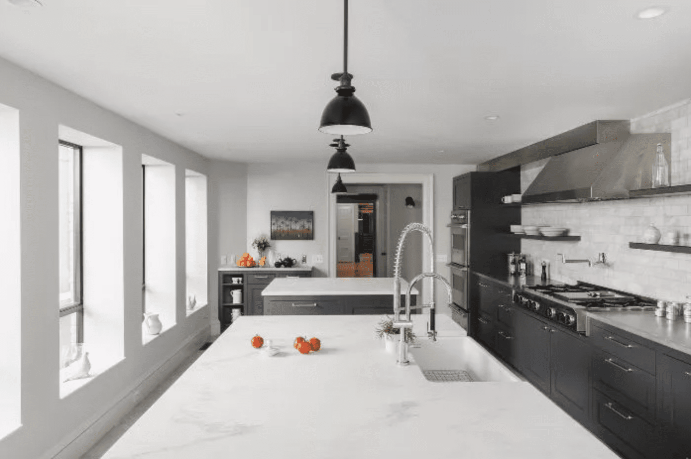 All white kitchen with black pendant lights and dark cabinetry