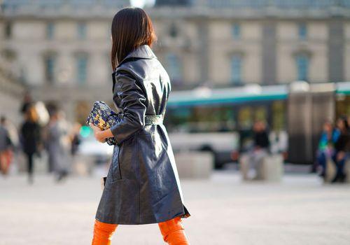 Mujer joven en abrigo negro alejándose