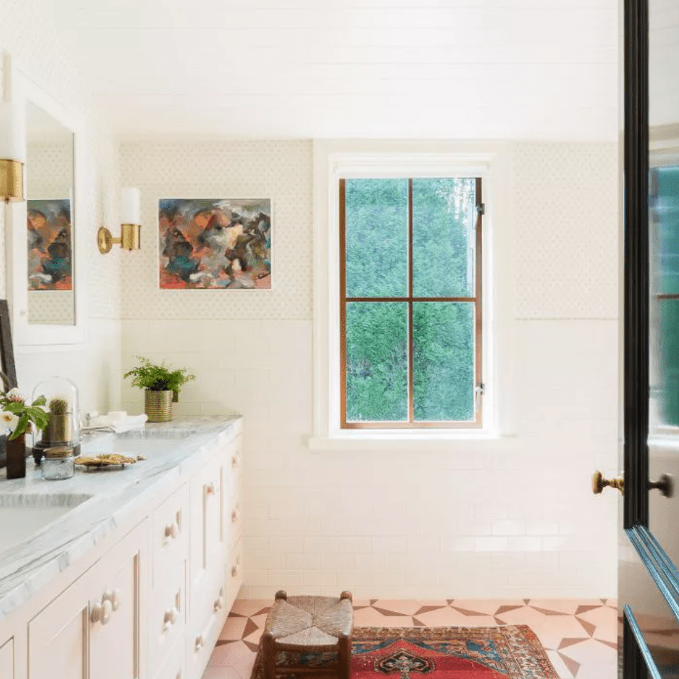 Tiled bathroom with woven step-stool and sconce lighting