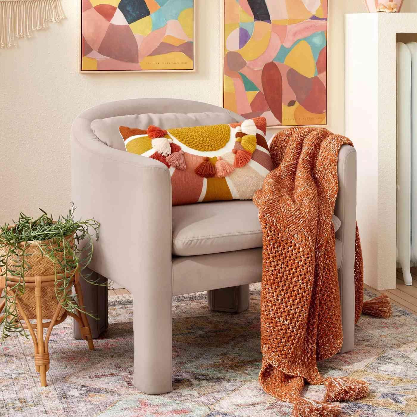 Embroidered Sun Lumbar Throw Pillow on chair.