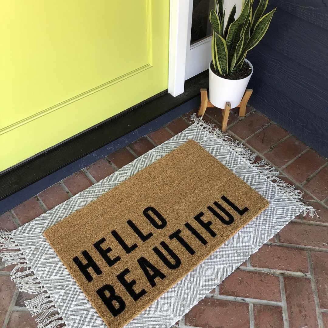 Hello Beautiful Doormat in front of yellow door.