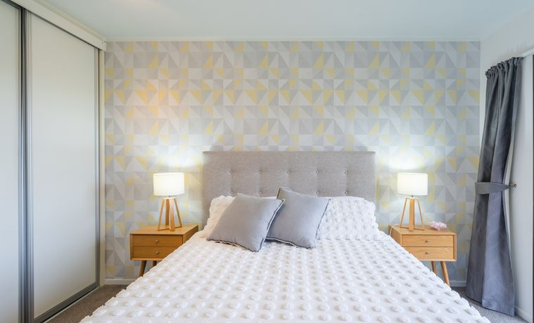 small bedroom, decorative pale yellow and blue triangle wallpaper on one wall, wooden bedside table on either side of bed