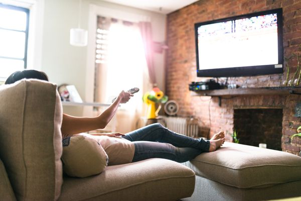 woman laying on couch watching tv with remote in hand