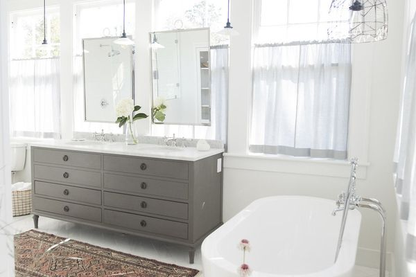 White and clean bathroom with tub and stools.