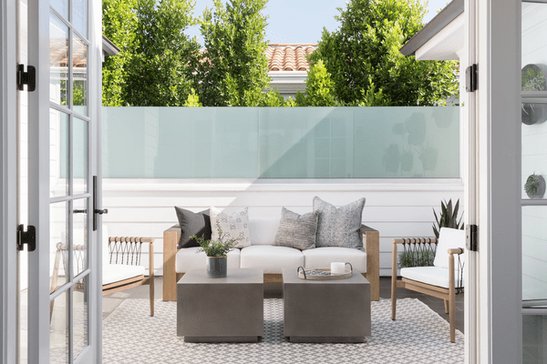 Open outdoor space with couch and concrete tables.
