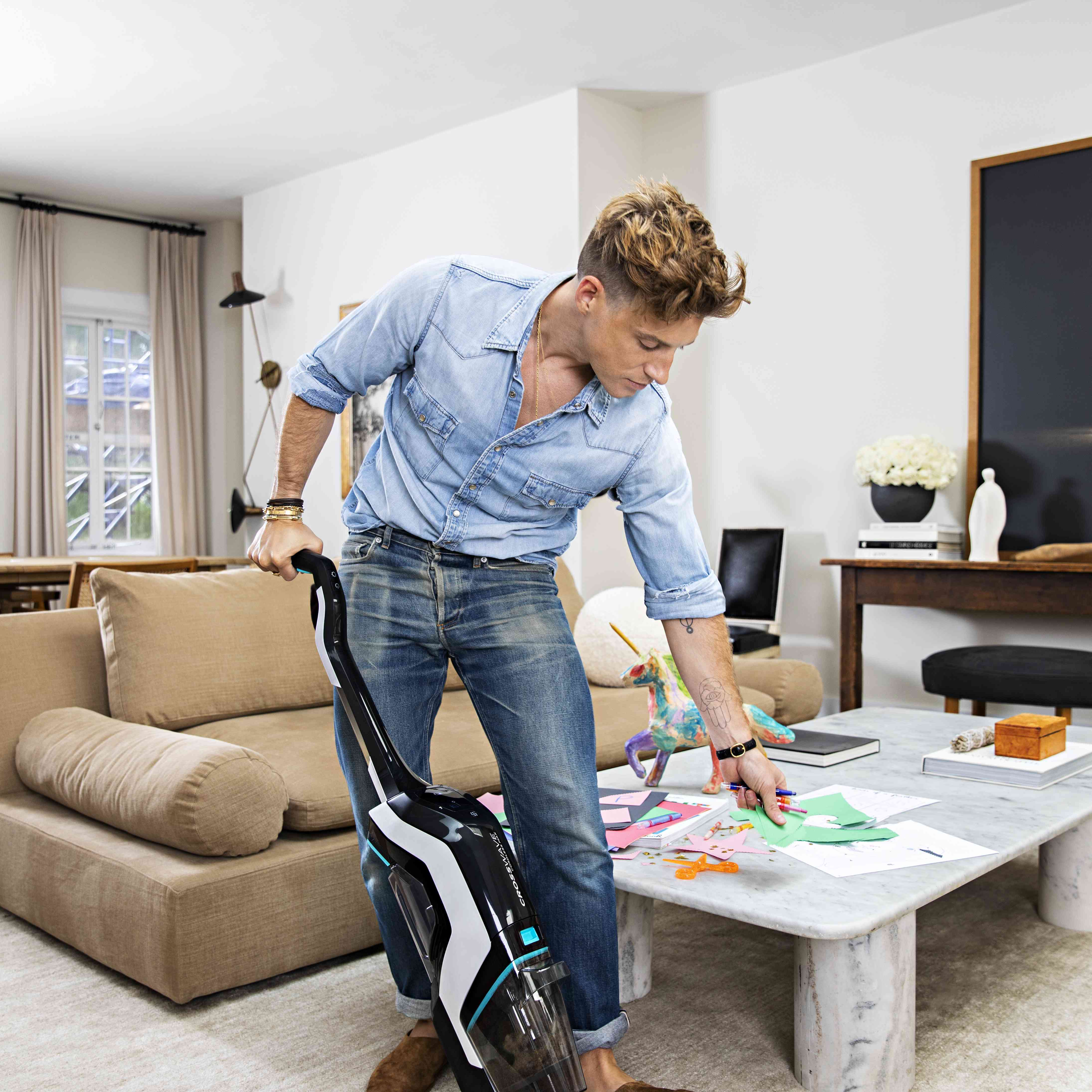 Jeremiah Brent using BISSELL CrossWave Cordless Max to clean up after arts and crafts project