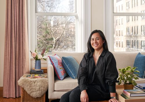 Wovn home founder Davina Ogilvie sits on an ottoman in her living room