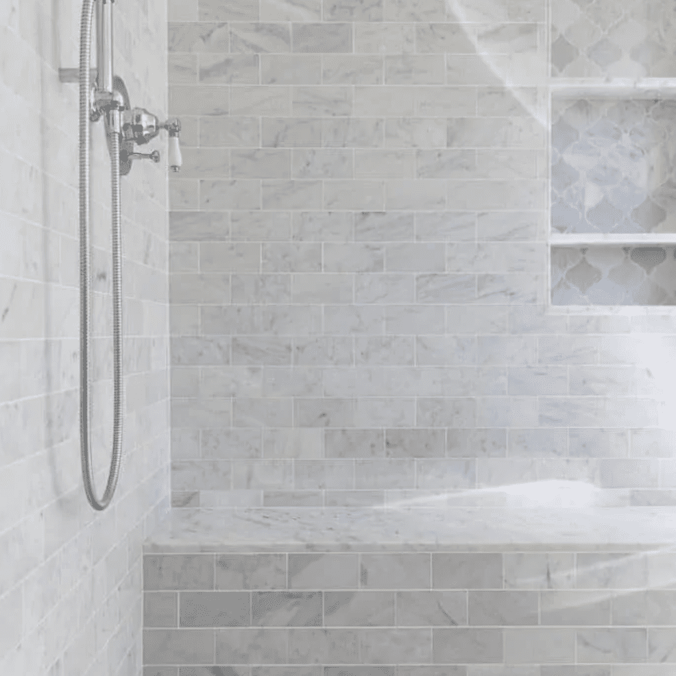 A shower lined with light gray tiles