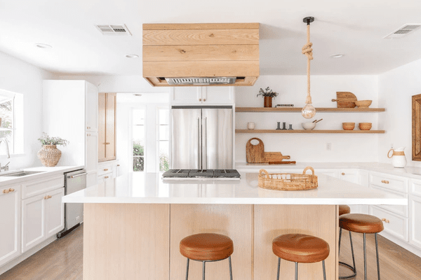A monochromatic kitchen with some light-stained wood pieces, some warmer wood pieces, and a few darker brown accents