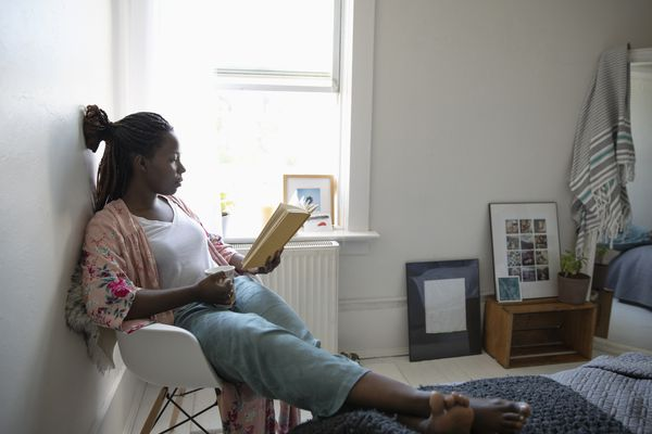 Young woman relaxing, drinking coffee and reading book in bedroom