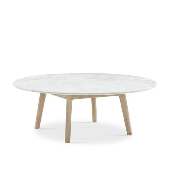 A low-slung modern Scandi-style round marble table with wooden legs.