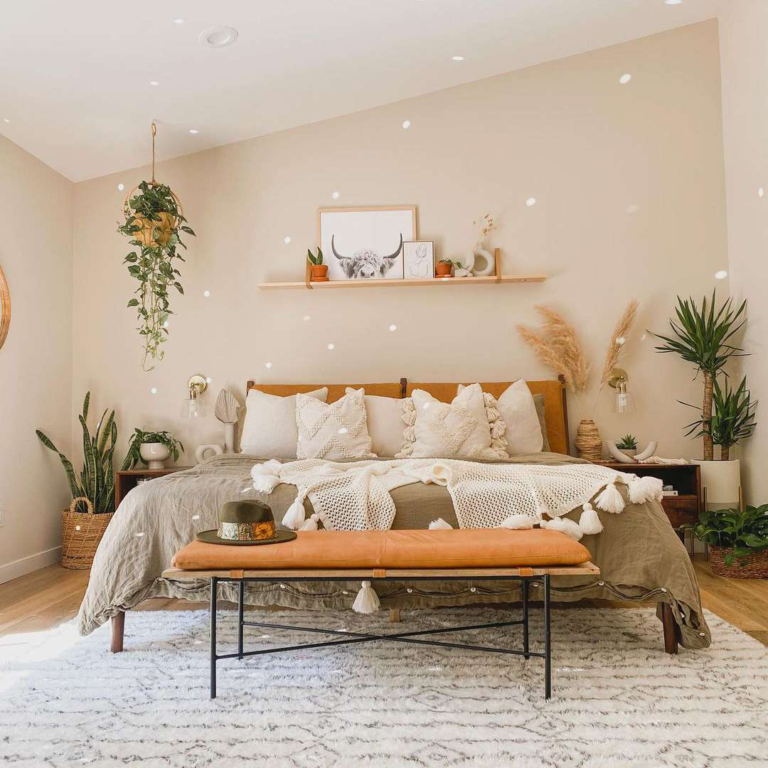 Neutral boho style bedroom with beige accent wall.