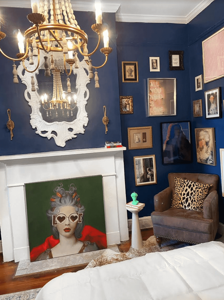 Navy sitting room with lots of art and ornate chandelier.