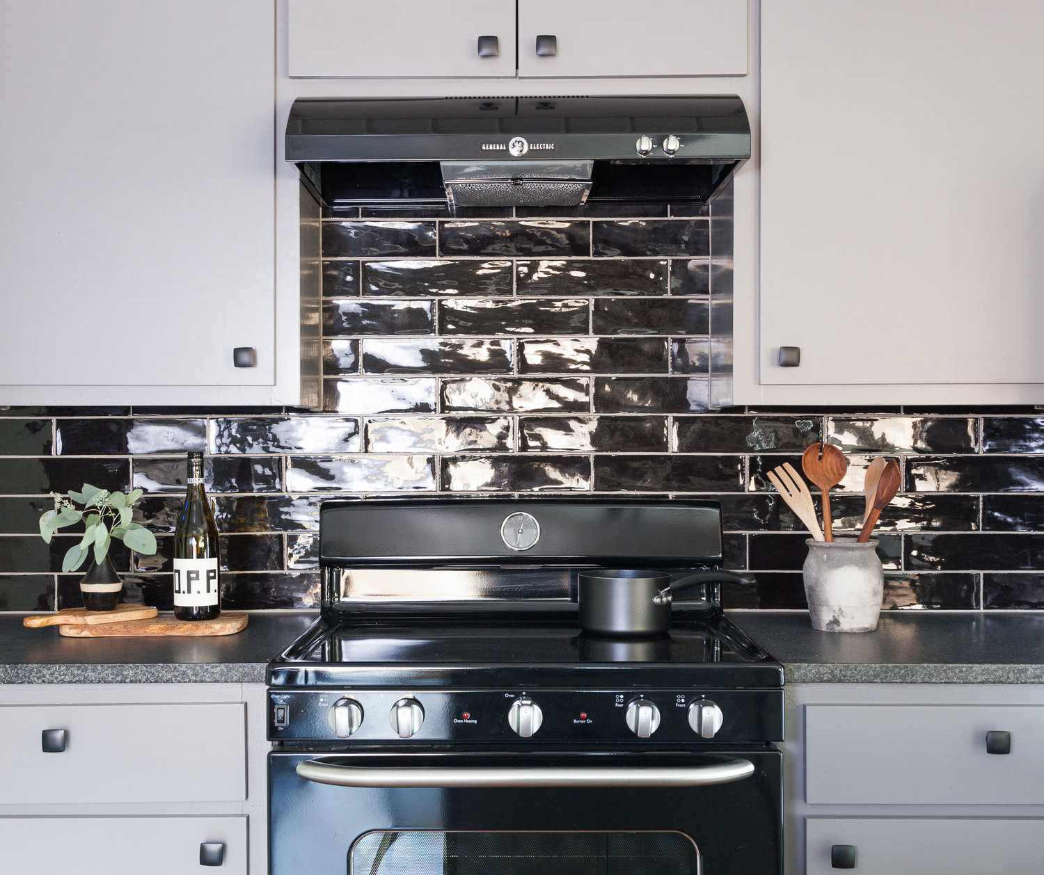A kitchen with gray kitchen cabinets and a black tiled backsplash