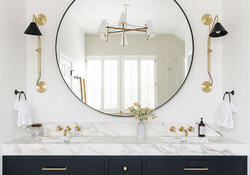 A bathroom with a marble countertop and built-in backsplash