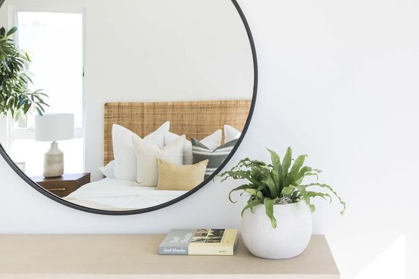 Round mirror over a dresser with a bed reflected